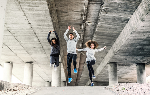 A group of young sporty friends jumping outside under the bridge in the city, doing exercise. - gettyimageskorea