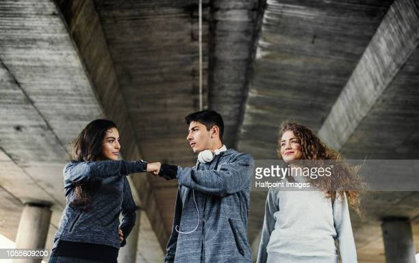 A group of young sporty friends standing outside under the bridge in the city, resting after doing exercise.