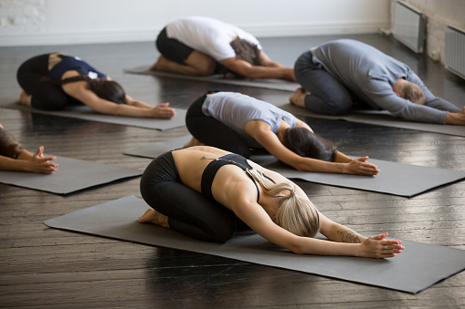 Group of young sporty people in Balasana pose 944619732
