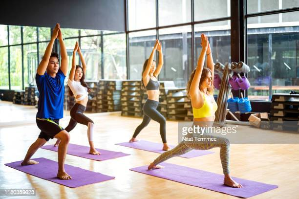 group of young sporty people practicing yoga lesson. - leisure facilities stock pictures, royalty-free photos & images