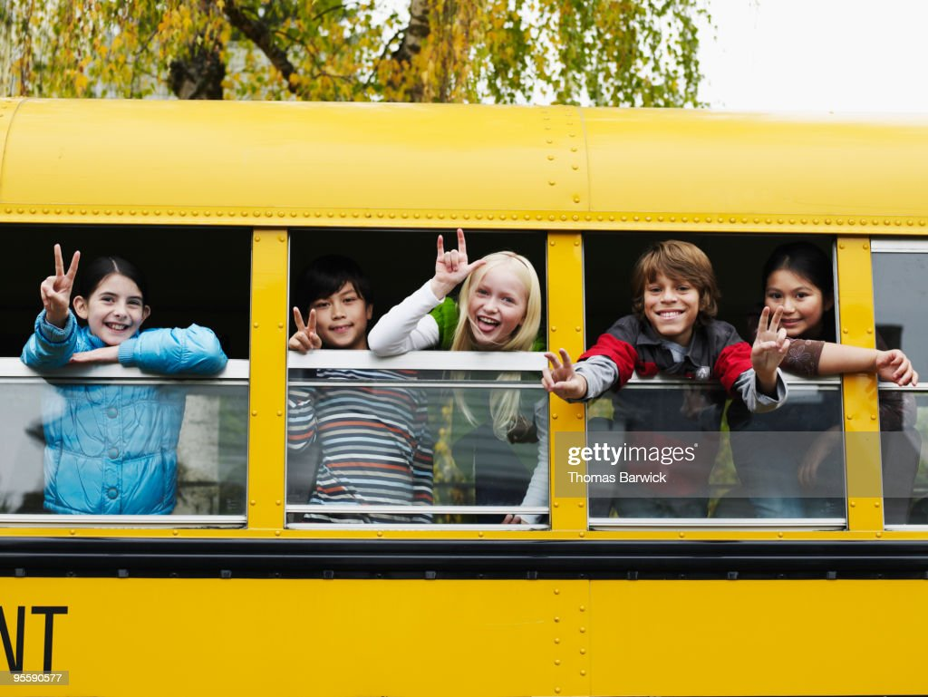 Group of young students hanging out bus windows : Stock Photo
