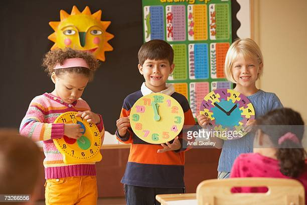Group of young students holding up clocks in front of class