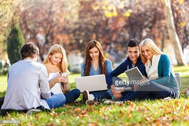 Gruppe von jungen Studenten mit Laptop, Tablet PC und Smartpho
