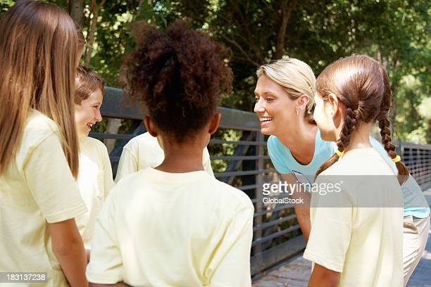 Group of young students with their teacher smiling - outdoor