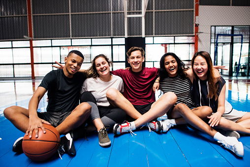 Group of young teenager friends on a basketball court relaxing portrait 938338032