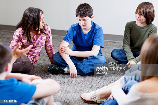 Group of young teens holding discussion in a circle
