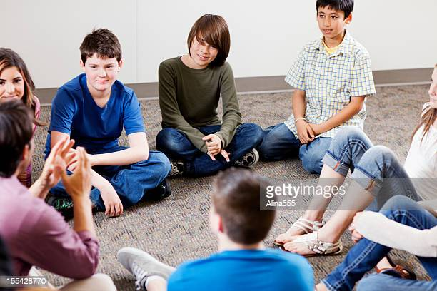 group of young teens listening to teacher - girl sitting on boys face stock photos and pictures