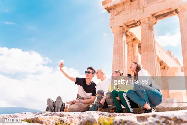 group of young tourists in acropolis - athens - athens greece stock pictures, royalty-free photos & images