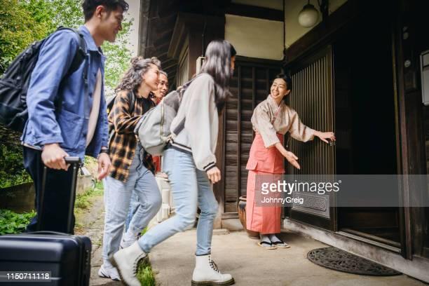 日本の伝統的旅館に到着する若い旅行者のグループ - 観光客 ストックフォトと画像
