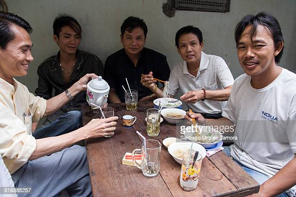 A group of young Vietnamese hairdressers having a relaxed breakfast together in a street of Phnom Penh SouthCentral Region Cambodia