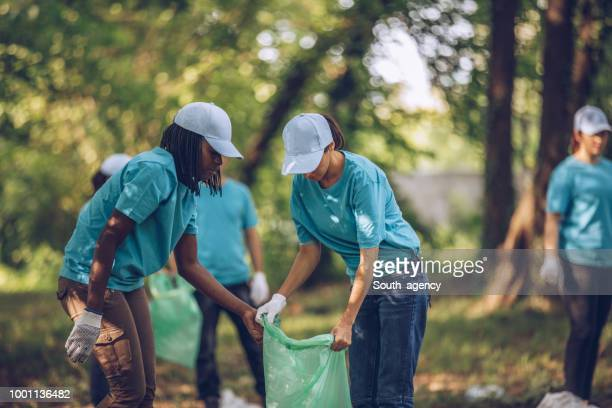 group of young volunteers collecting garbage in nature - community outreach stock pictures, royalty-free photos & images