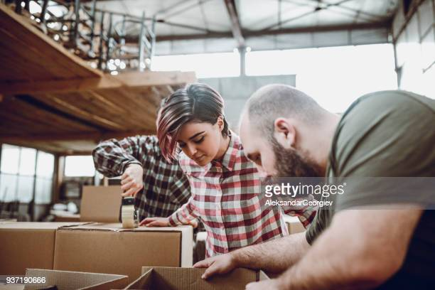 group of young warehouse workers packing boxes for shipment - tape dispenser stock photos and pictures