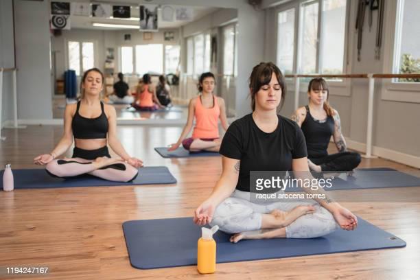 group of young white women meditating in yoga studio with natural light - lagsport bildbanksfoton och bilder