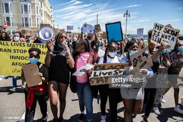 A group of young women are seen holding placards and mega phone during the BLM protest in Brighton Local activists in England organised a protest in...