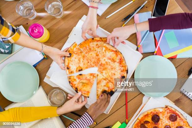 Group of young women at home sharing a pizza