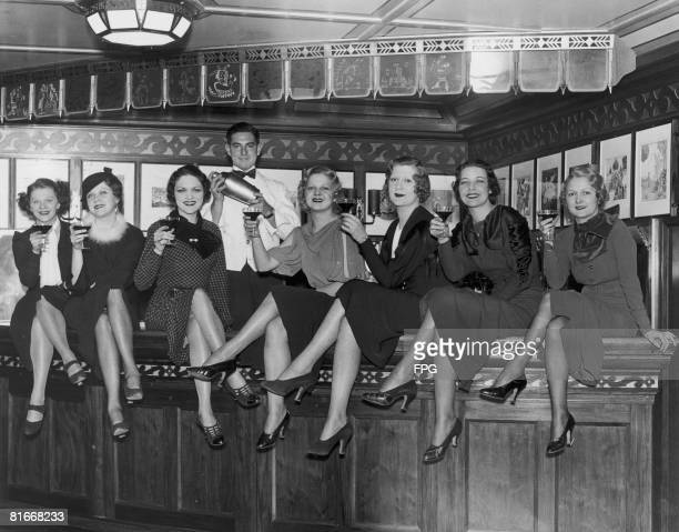 Group of young women at the bar on board the luxury liner SS Manhattan, off New York, 5th December 1933. Before the repeal of prohibition, the ship's...