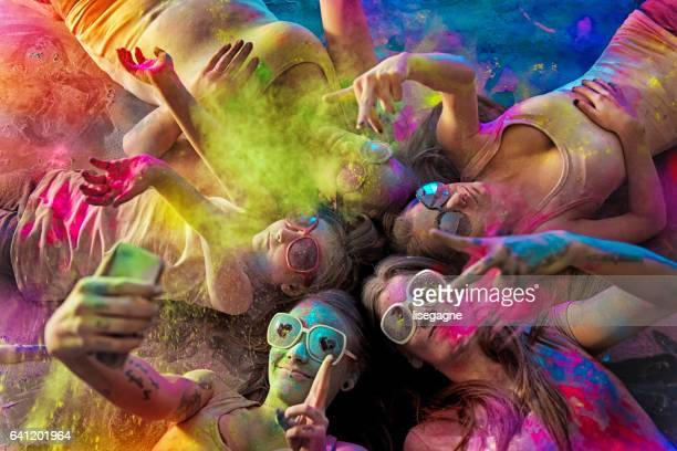 group of young women covered with holi powder - holi stock pictures, royalty-free photos & images