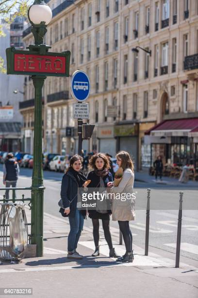 group of young women friends walking in paris - paris metro sign stock pictures, royalty-free photos & images