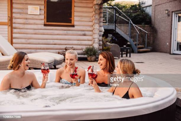 Group of young women having fun in hot tub whirlpool outdoors