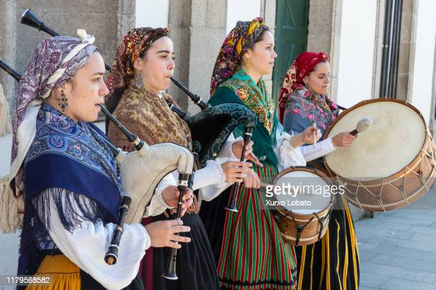 A group of young women in traditional costumes play Galician music with bagpipes tambourines and drum in the historic center during the San Froilan...