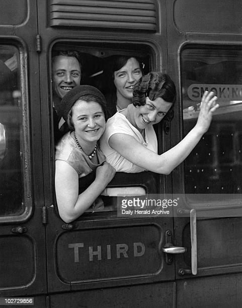 A group of young women looking out of a railway carriage 3 July 1931 Women waving goodbye from a third class carriage window at Victoria Station...