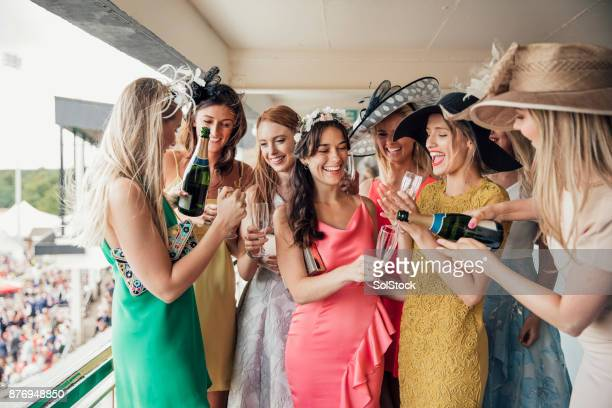 group of young women opening a bottle of champagne - horse racing stock pictures, royalty-free photos & images