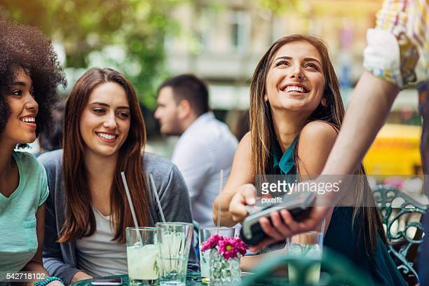 Eine Gruppe von jungen Frauen, die mit Kreditkarte im bistro