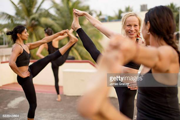 A group of young women practice and perform their daily routine of yoga on a rooftop