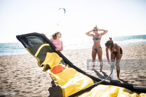 group of young women preparing for kitesurfing on the beach. - air pump stock photos and pictures