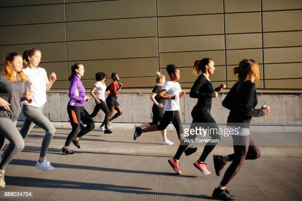 group of young women running in city setting
