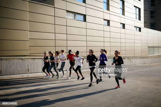 group of young women running in the city - center athlete stock pictures, royalty-free photos & images