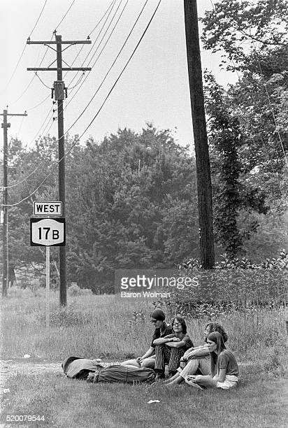 Group of young women sit on the grass next to the 17B West Road at the Woodstock Music & Art Fair, Bethel, NY, August 15, 1969.