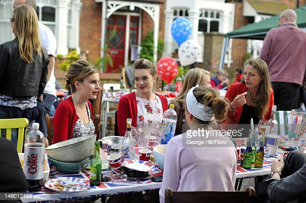 Group of young women sitting chatting whilst surrounded by union jack cups and plates and at the end of a street party held by the residents of...