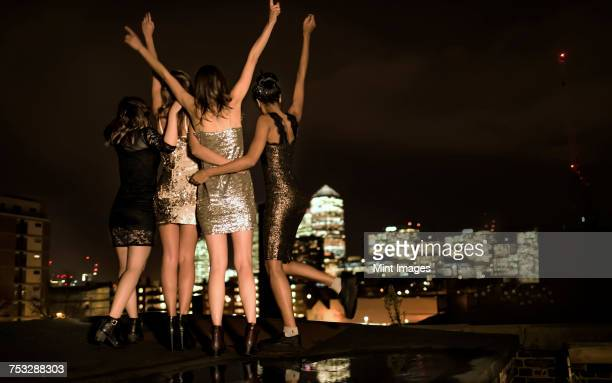 group of young women standing on a rooftop celebrating. - vida nocturna fotografías e imágenes de stock