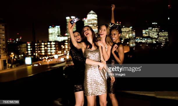 group of young women standing on a rooftop posing for a photograph. - cocktail dress stock pictures, royalty-free photos & images