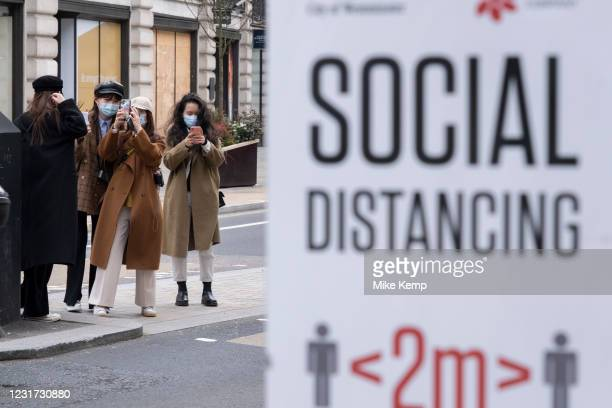 Group of young women take selfies and pictures of one another near to a social distancing sign on regent Street as the national coronavirus lockdown...