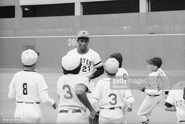 A group of youngsters from Puerto Rico flock to Pirates star Roberto Clemente during the filming of a commercial at Three Rivers Stadium