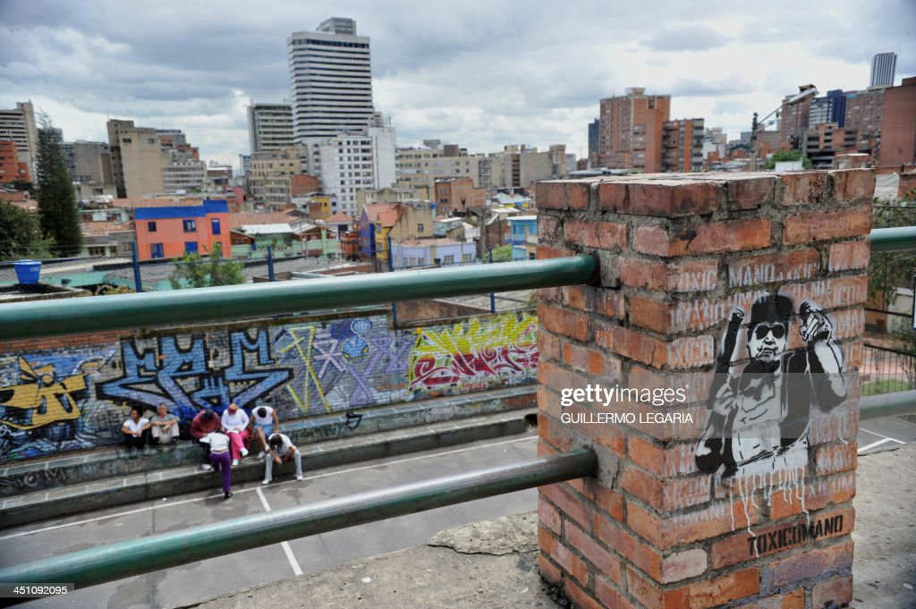 A group of youngsters sit against a graffiti painted as a stencil by Toxicomano is seen wall in Bogota, Colombia, on July 9, 2010. AFP PHOTO/Guillermo LEGARIA /