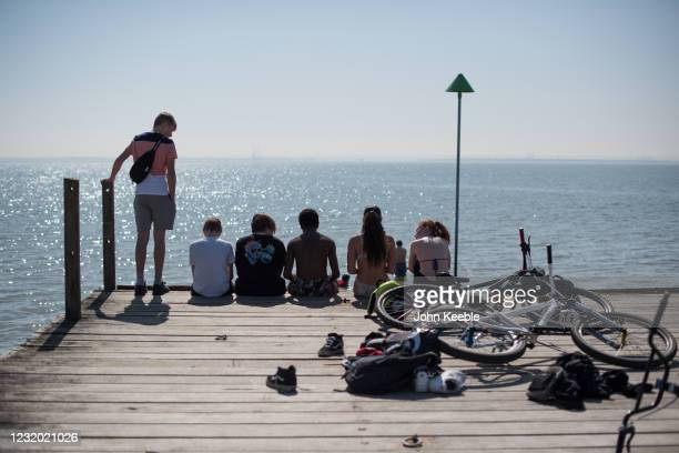 Group of youngsters sit on the end of a jetty with their bikes on March 30, 2021 in Southend, United Kingdom. Despite todays temperature heading...