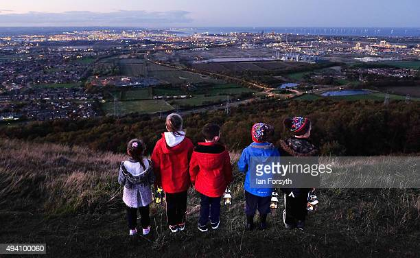 A group of youngsters stand with lanterns during a torchlit procession on the top of the Eston Hills overlooking Teesside on October 24 2015 in Eston...