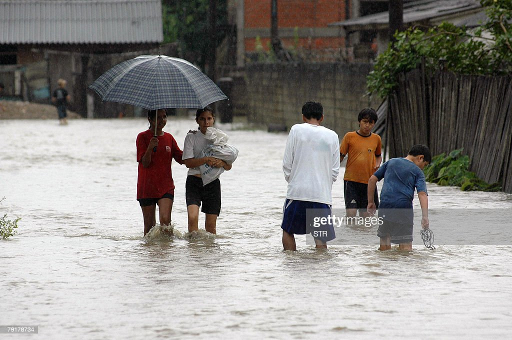 A group of youngsters walk in a flooded street in Villarroel, some 270km east of Cochabamba, center Bolivia, after the overflowing of the Ichilo and Sajta rivers, 23 January, 2008. The Bolivian government decreed on Tuesday a national emergency to counteract damages caused by heavy rains and floods battering the country since last November. According to last official sources, 27 people died so far, four are still missing and about 21,500 families have been seriously damaged.