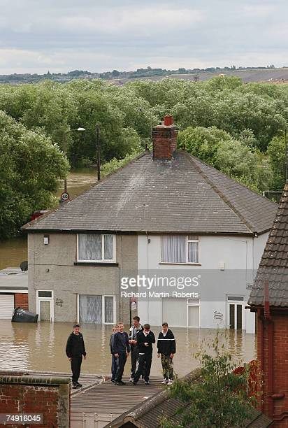 A group of youths find a dry spot as floodwater subsides in the Catcliffe area of Rotherham half a mile from the cracked Ulley Dam on June 26 2007 in...