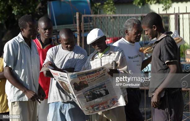 A group of Zimbabwean's read a local newspaper The Herald looking for results of the weekend election in the Mbere suburb of Harare on April 01 2008...