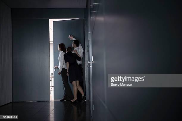 group peeking through gap in door