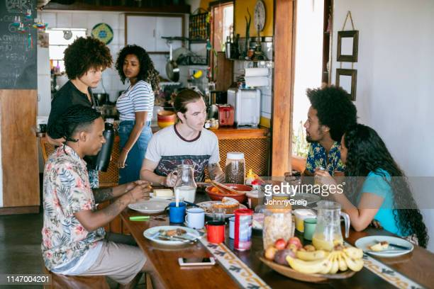 group people eating food in communal kitchen at guesthouse - hostel stock pictures, royalty-free photos & images