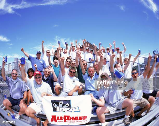 Group photo of fans holding a sign as they sit on Murphy's bleachers over looking Wrigley Field during a game between the Philadelphia Phillies and...