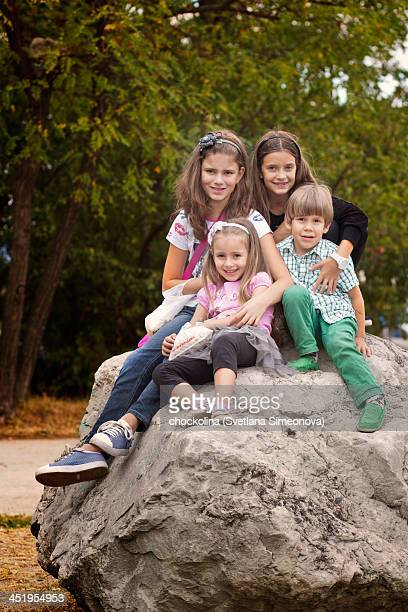 Group photo of four children sitting on a rock