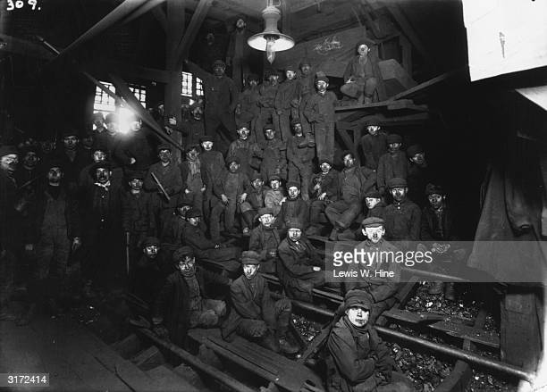 Group photo of many young male mine workers sitting on wooden bleachers with their faces clothes and caps covered with dirt Men stand on the side of...