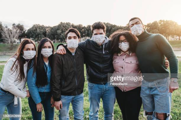 group photo of six friends wearing masks to protect themselves from viruses - mascherina chirurgica foto e immagini stock
