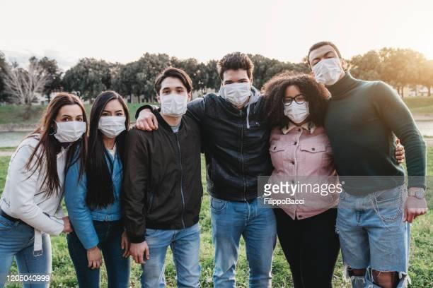 gruppenfoto von sechs freunden, die masken tragen, um sich vor viren zu schützen - mittelgroße personengruppe stock-fotos und bilder
